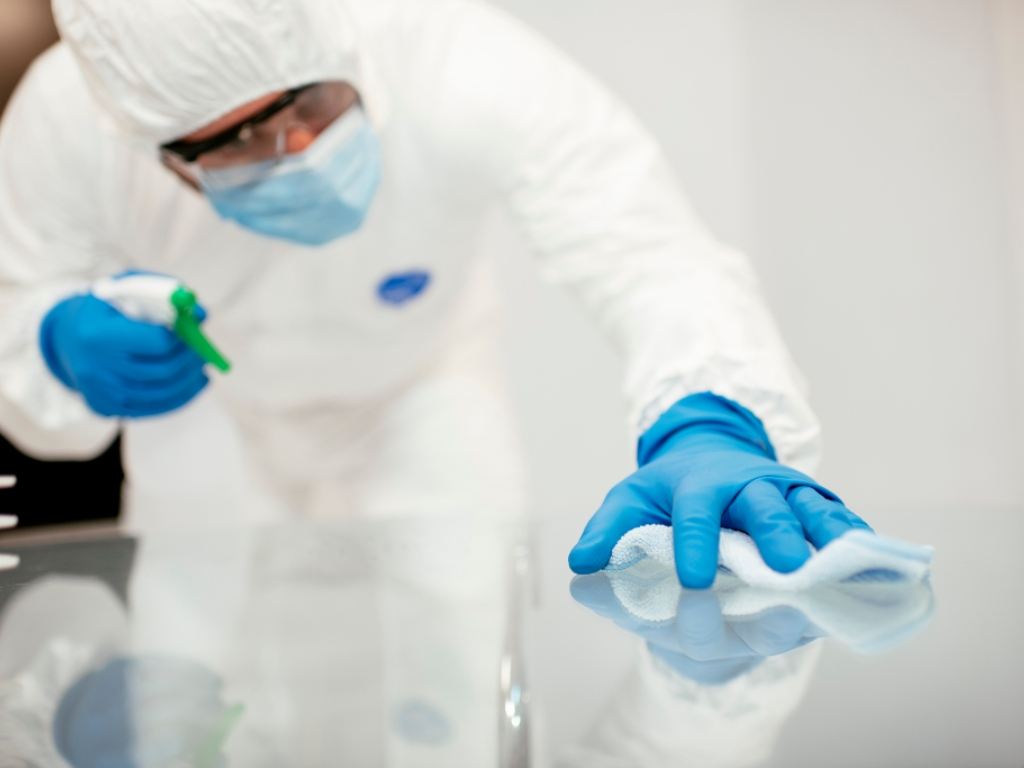 Man performing GMP cleaning. He is wearing a clean suit and blue gloves and is disinfecting a metal surface.